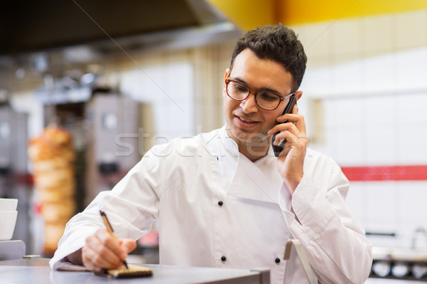 Stock photo: chef at kebab shop calling on smartphone
