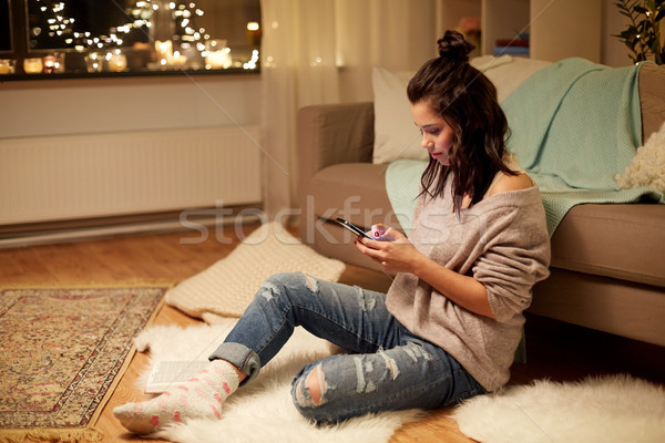 happy young woman with smartphone at home Stock photo © dolgachov