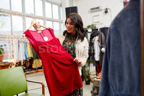 happy woman choosing dress at clothing store Stock photo © dolgachov
