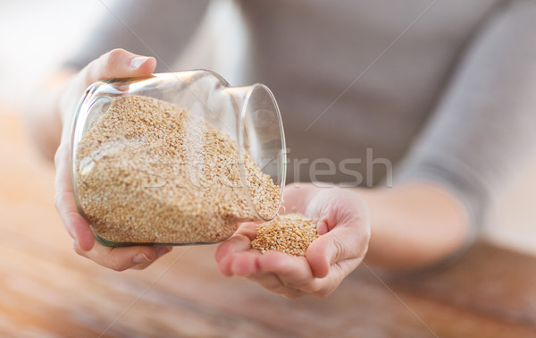 close up of female emptying jar with quinoa Stock photo © dolgachov