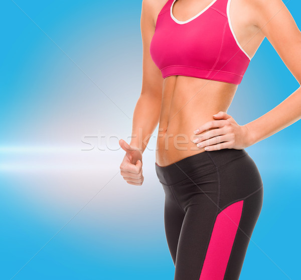 close up of female abs and hand showing thumbs up Stock photo © dolgachov
