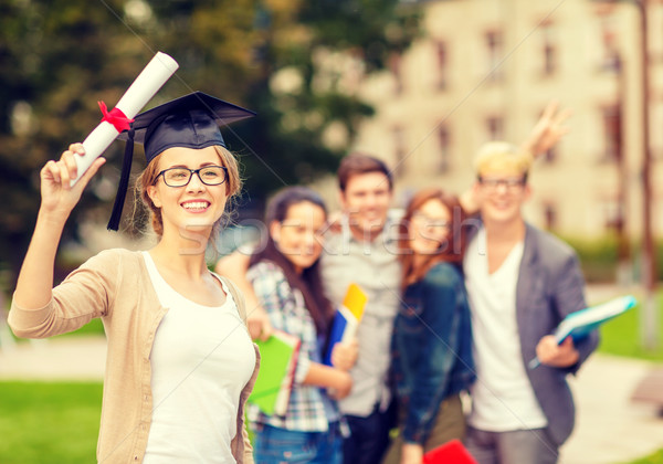 smiling teenage girl in corner-cap with diploma Stock photo © dolgachov