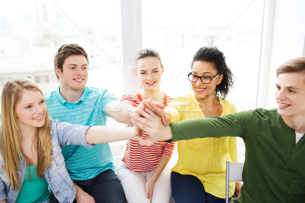 smiling students making high five gesture sitting Stock photo © dolgachov
