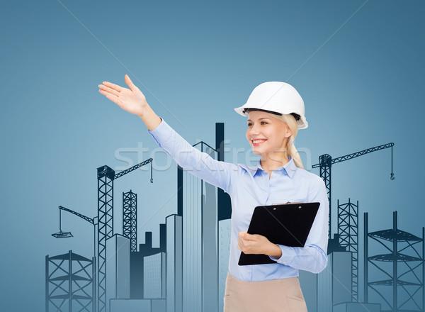 Foto stock: Sorridente · empresária · capacete · clipboard · edifício · em · desenvolvimento