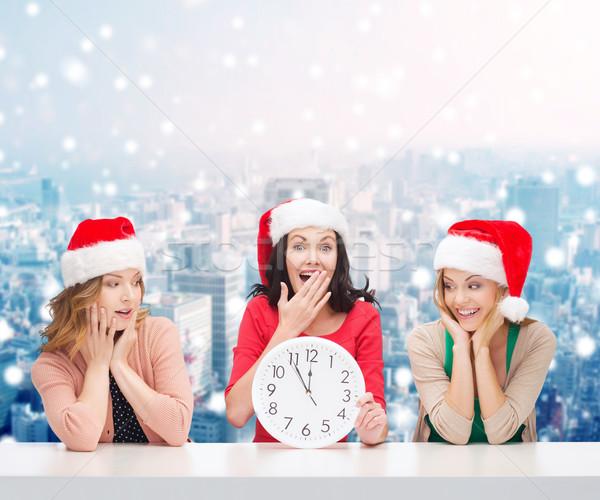 smiling women in santa helper hats with clock Stock photo © dolgachov