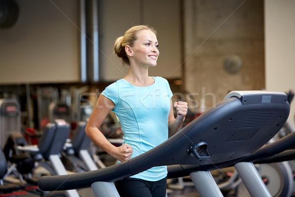 Glimlachende vrouw tredmolen gymnasium sport fitness Stockfoto © dolgachov
