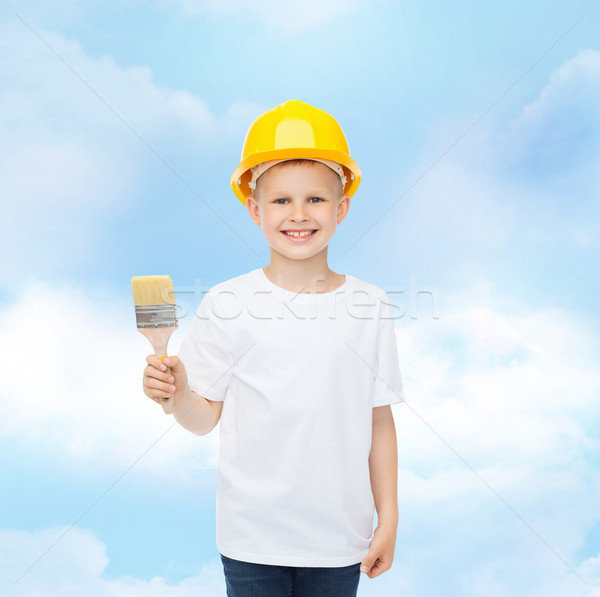 smiling little boy in helmet with paint brush Stock photo © dolgachov