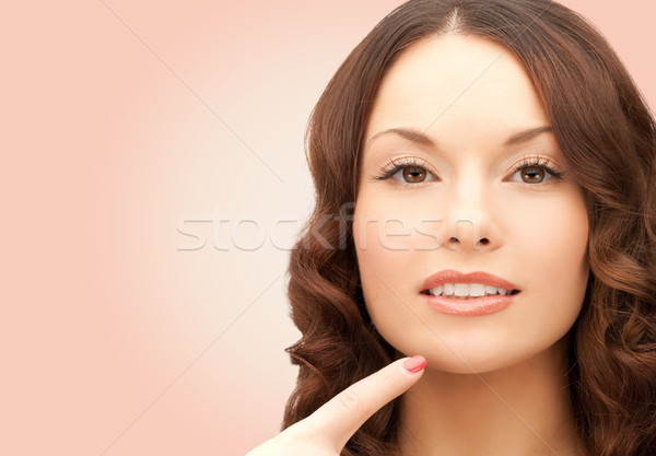 beautiful young woman pointing finger to her chin Stock photo © dolgachov