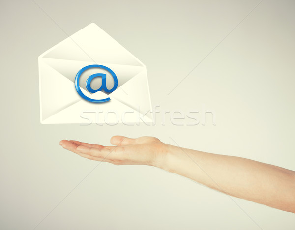 Stock photo: hand holding envelope with email sign
