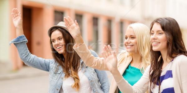 three beautiful girls waving hands Stock photo © dolgachov