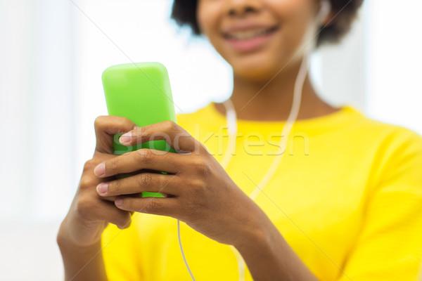 счастливым африканских женщину смартфон наушники люди Сток-фото © dolgachov