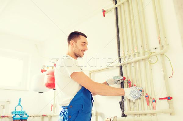 smiling builder or plumber working indoors Stock photo © dolgachov
