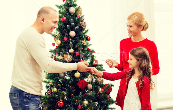 Stock photo: smiling family decorating christmas tree at home