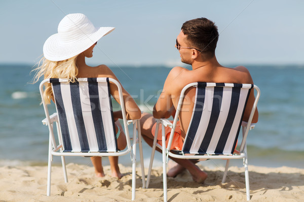 happy couple sunbathing in chairs on summer beach Stock photo © dolgachov