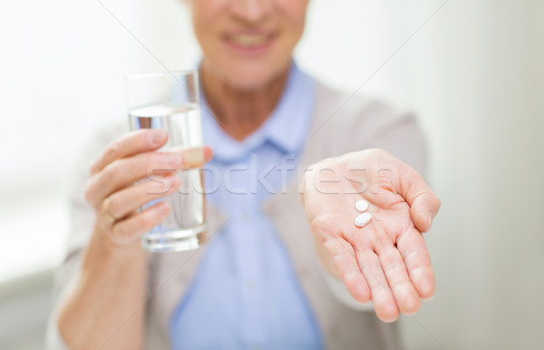 close up of senior woman with water and pills Stock photo © dolgachov