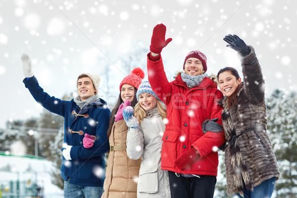 happy friends waving hands on ice rink outdoors Stock photo © dolgachov