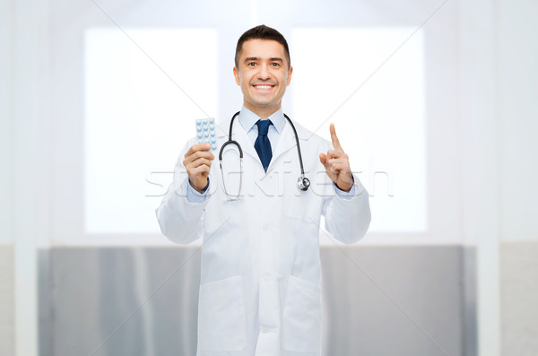 smiling male doctor in white coat with pills Stock photo © dolgachov