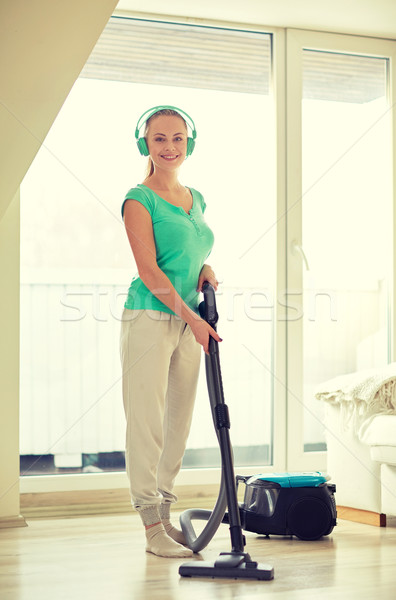 happy woman in headphones with vacuum cleaner Stock photo © dolgachov