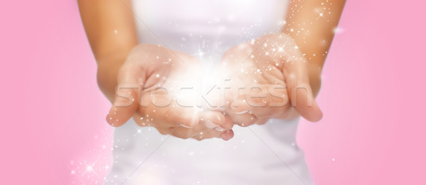 Stock photo: magic twinkles or fairy dust on female hands