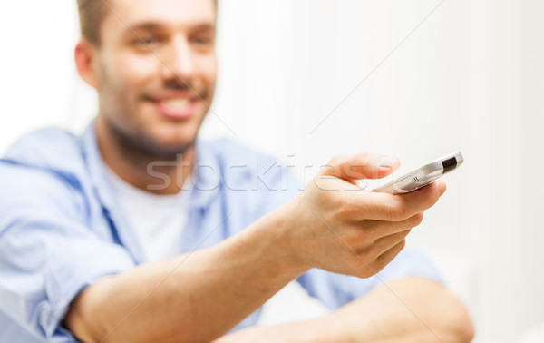 close up of man with tv remote control at home Stock photo © dolgachov