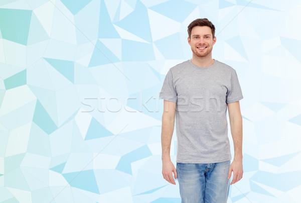 Mutlu gülen genç gri tshirt kot Stok fotoğraf © dolgachov
