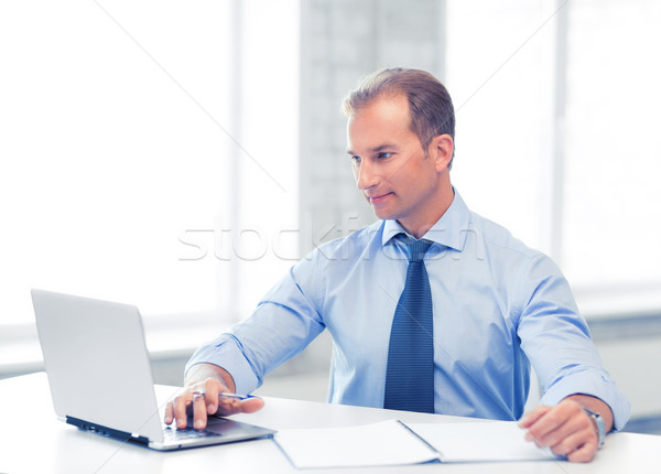 miling businessman working in office Stock photo © dolgachov