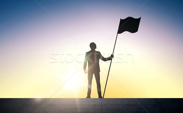 Silhouette imprenditore bandiera sole luce business Foto d'archivio © dolgachov