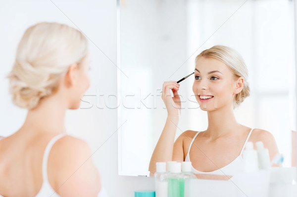 woman with brush doing eyebrow makeup at bathroom Stock photo © dolgachov