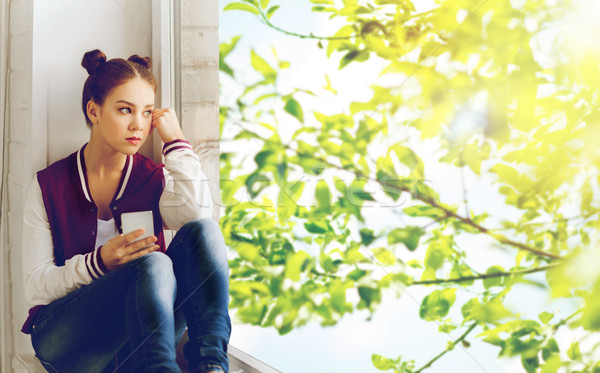 teenage girl sitting on windowsill with smartphone Stock photo © dolgachov