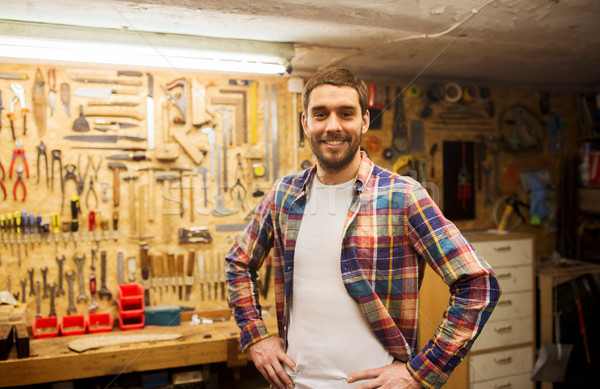 happy young workman in checkered shirt at workshop Stock photo © dolgachov