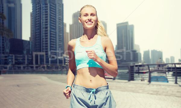 woman running or jogging over dubai city street Stock photo © dolgachov