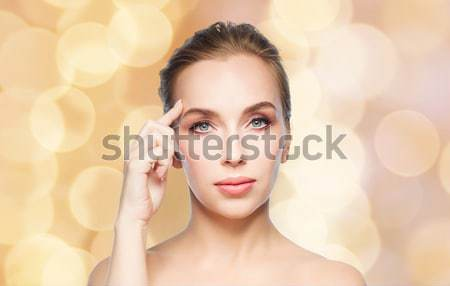 beautiful woman pointing at her forehead Stock photo © dolgachov