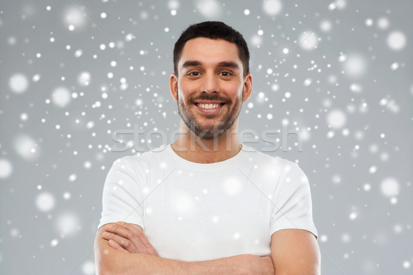 smiling man with crossed arms over snow background Stock photo © dolgachov
