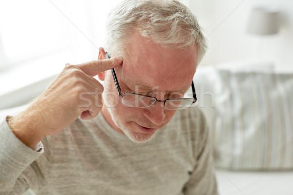 senior man suffering from headache at home Stock photo © dolgachov