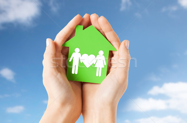 hands holding green house with family pictogram Stock photo © dolgachov