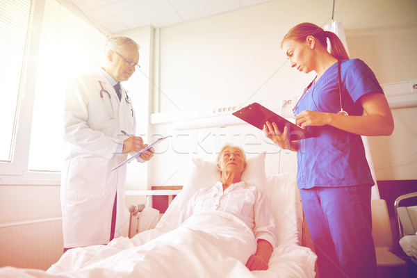 Stock photo: doctor and nurse visiting senior woman at hospital