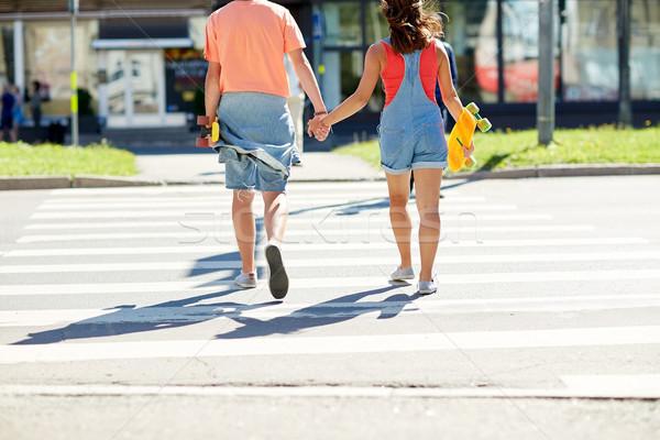 teenage couple with skateboards at city crosswalk Stock photo © dolgachov