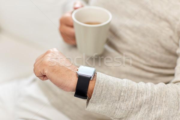 close up of senior man with tea and wristwatch Stock photo © dolgachov