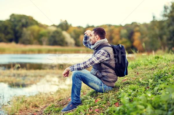 Sonriendo hombre mochila río banco Foto stock © dolgachov