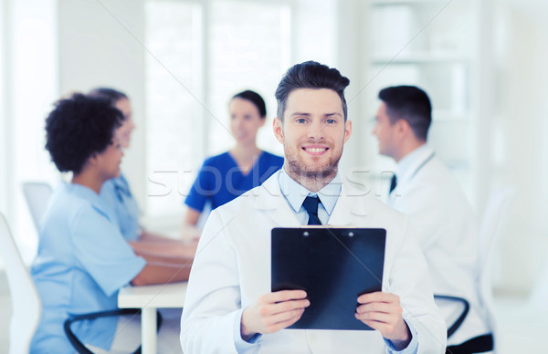 Stock photo: happy doctor with tablet pc over team at clinic