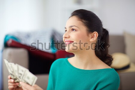 happy woman with money planning her travel at home Stock photo © dolgachov