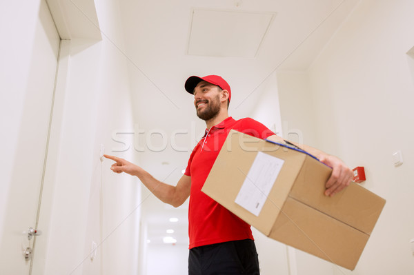 delivery man with parcel box ringing doorbell Stock photo © dolgachov
