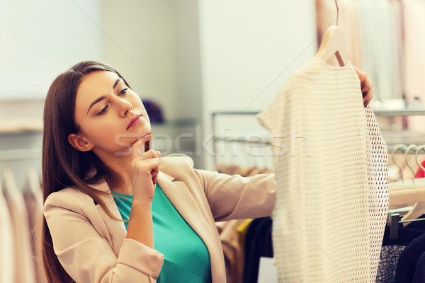 thoughtful young woman choosing clothes in mall Stock photo © dolgachov