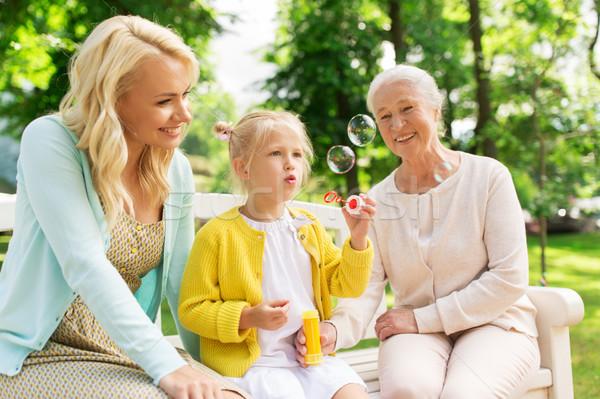 happy family blowing soap bubbles at park Stock photo © dolgachov
