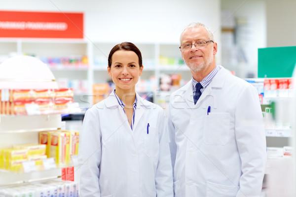 happy apothecaries at pharmacy Stock photo © dolgachov