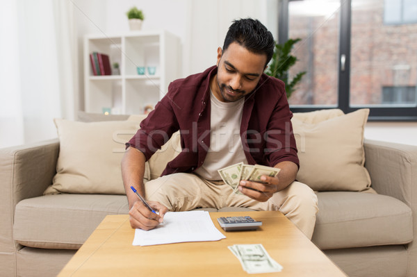 man with money and calculator filling papers Stock photo © dolgachov