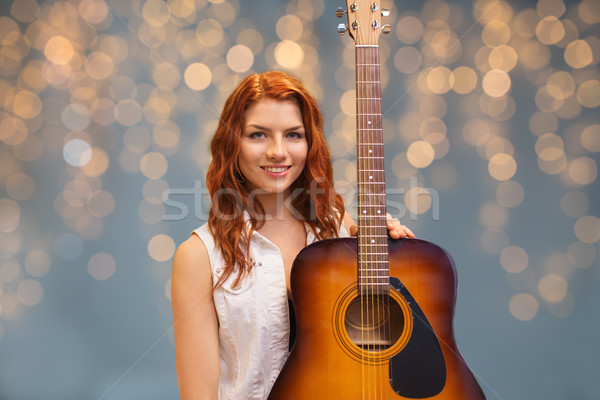 female musician with guitar over lights background Stock photo © dolgachov