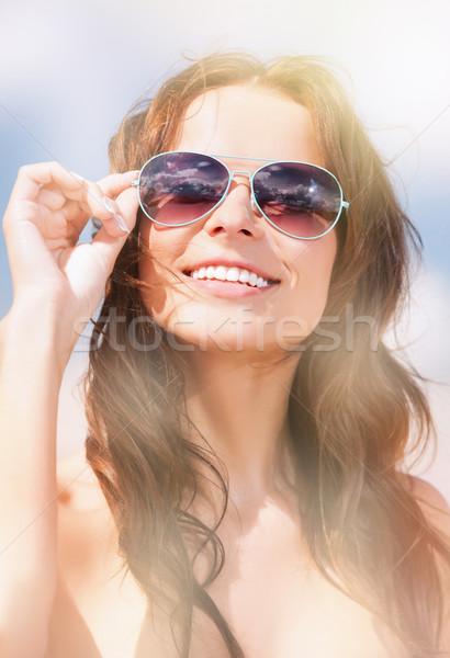 beautiful woman in sunglasses on a beach Stock photo © dolgachov