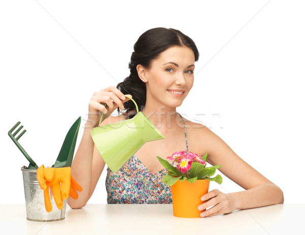 housewife with flower in pot and watering can Stock photo © dolgachov