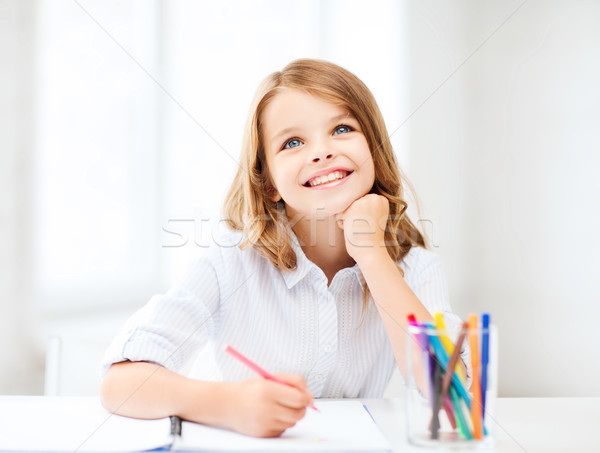 smiling little student girl drawing at school Stock photo © dolgachov